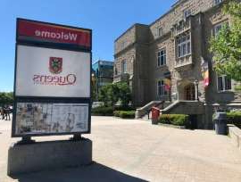 a building that has a sign on the side of a road: The note was found inside a Queen's University student residence on Thursday morning.