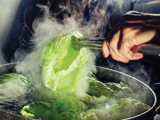a pan filled with meat and vegetables: A cook parboils cabbage for rolls.
