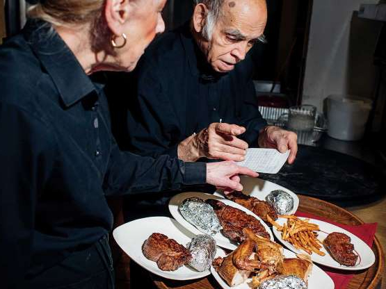 a person sitting at a table with a plate of food: Like Steve Elias (on left), much of the staff at Jamil's has worked here (or at other Lebanese steakhouses in town) for decades.