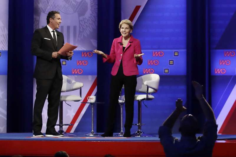 Elizabeth Warren, Chris Cuomo are posing for a picture: Sen. Elizabeth Warren (D-Mass.) speaks as CNN's  Chris Cuomo listens during Thursday's town hall on LGBTQ issues.