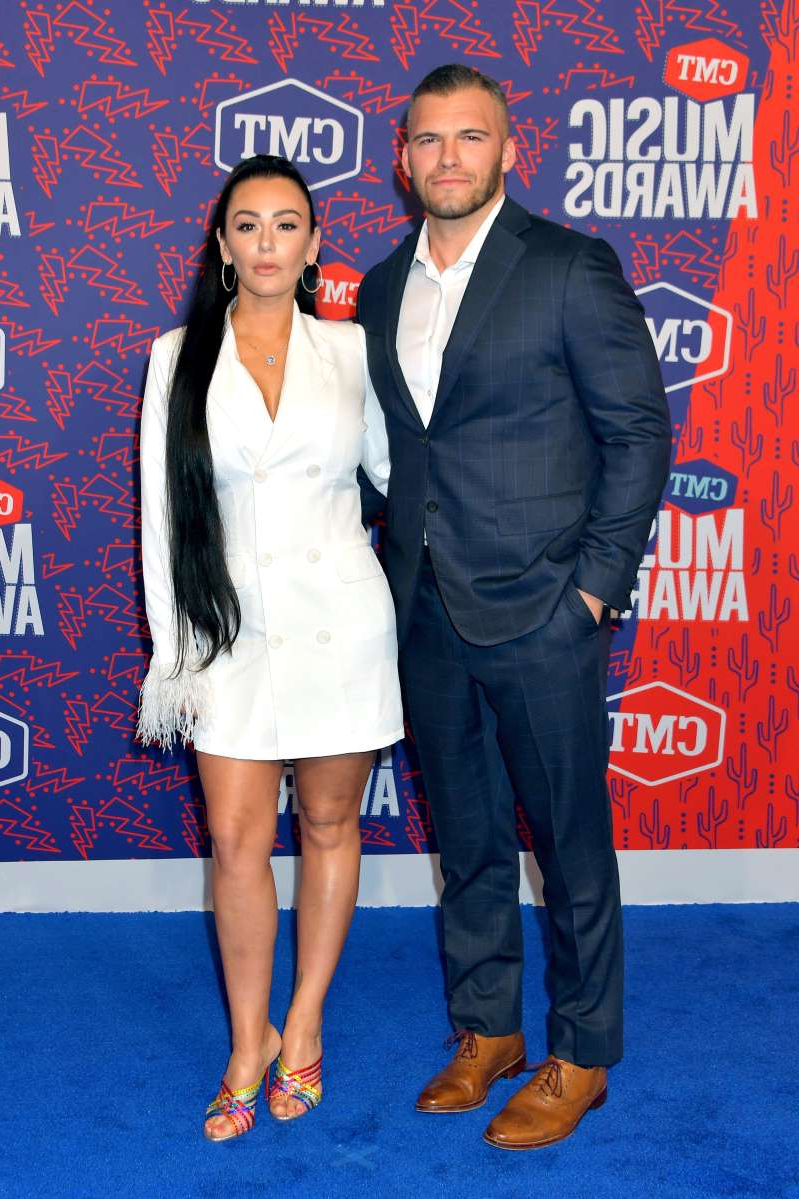JWoww holding a sign posing for the camera: Jenni Farley and Zack Clayton Carpinello attend the 2019 CMT Music Awards - Arrivals at Bridgestone Arena in Nashville, Tennessee on June 5, 2019.