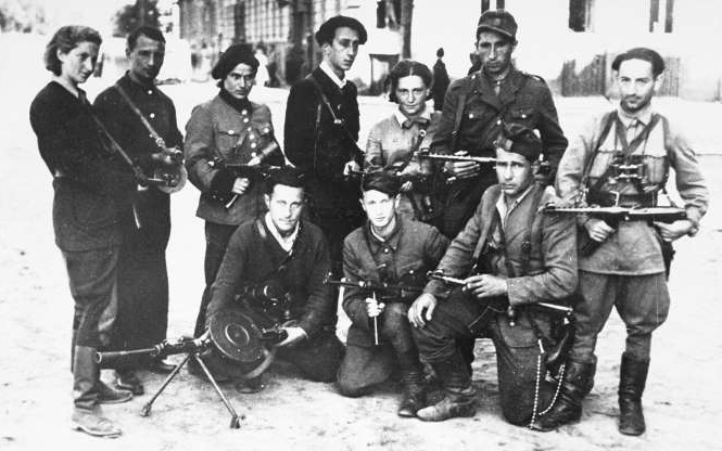 a group of people in uniform posing for a photo: Vitka Kempner(Far Right) led a group bent on vengeance in post-war Europe.