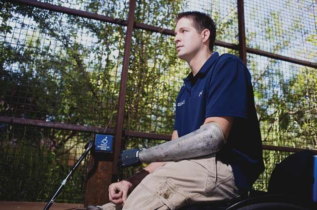 "a man standing next to a fence: Brian Kolfage, an Iraq War veteran who sought funding for a border wall, told me: ""We got $50,000 that first day, and we were like, 'Whoa, that was fast.' "" (Will Seberger / Zuma Press / Alamy)"