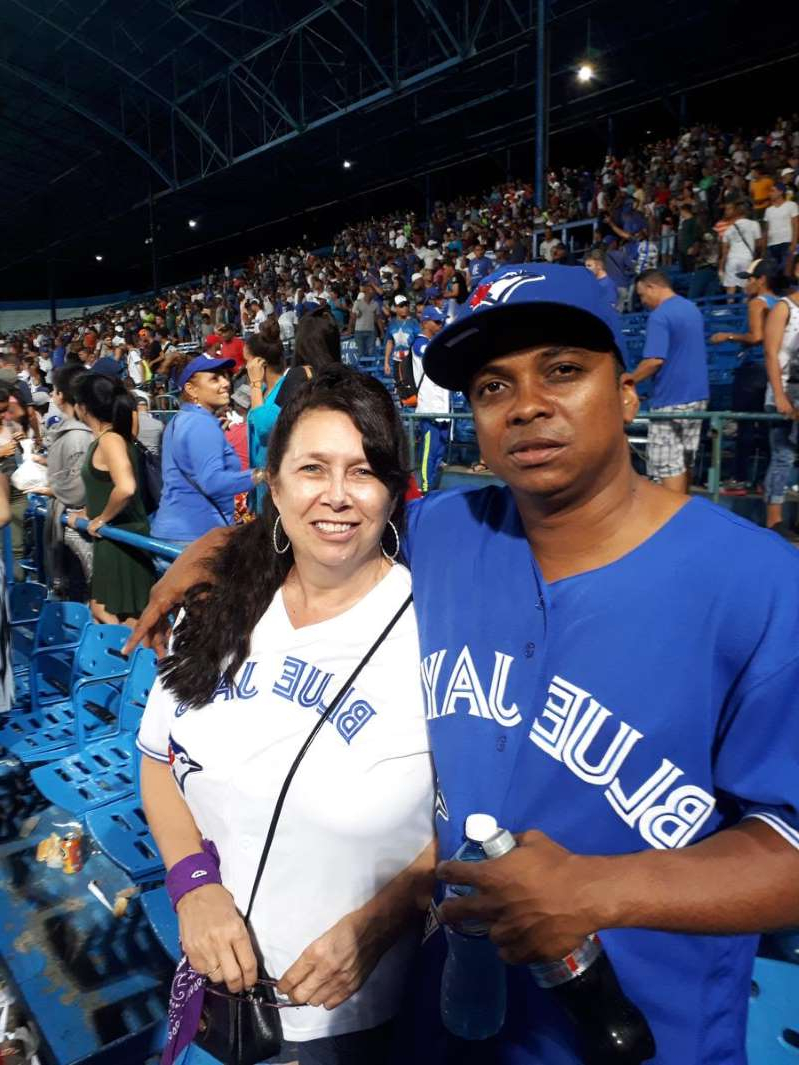a person standing in front of a crowd posing for the camera: Shirley Deveau is shown with her Cuban husband Abel Sarmiento Sosa, wearing a Toronto Blue Jays jersey, at the Stadium in Havana, cheering for the local Los Industriales team.