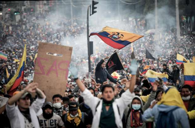 Slide 1 of 15: Numerous people fly flags of Ecuador and demand