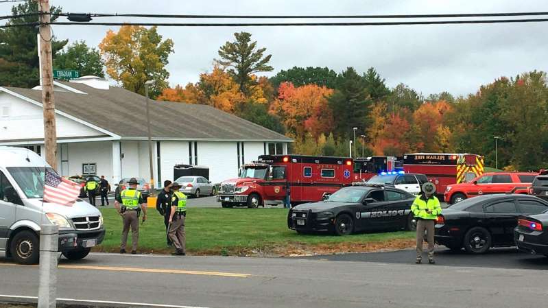 a group of police officers riding on the back of a truck: In this photo provided by WMUR-TV, police stand outside the New England Pentecostal Church after reports of a shooting on Oct. 12, 2019, in Pelham, N.H.