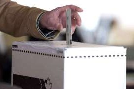 a hand holding a box: A ballot going into a voting box.
