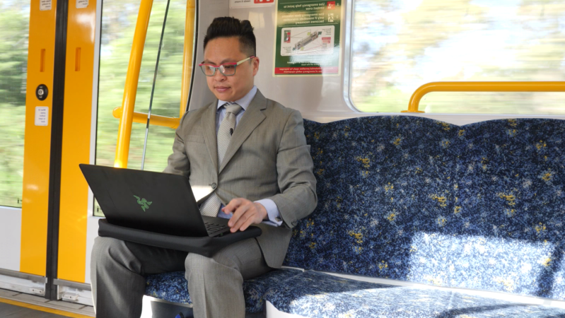 a person wearing a suit and tie sitting in front of a laptop: A return train trip and work in Sydney for Wollongong resident Harris Cheung takes up to 14 hours out of his day. (Justin Huntsdale, ABC Illawarra)