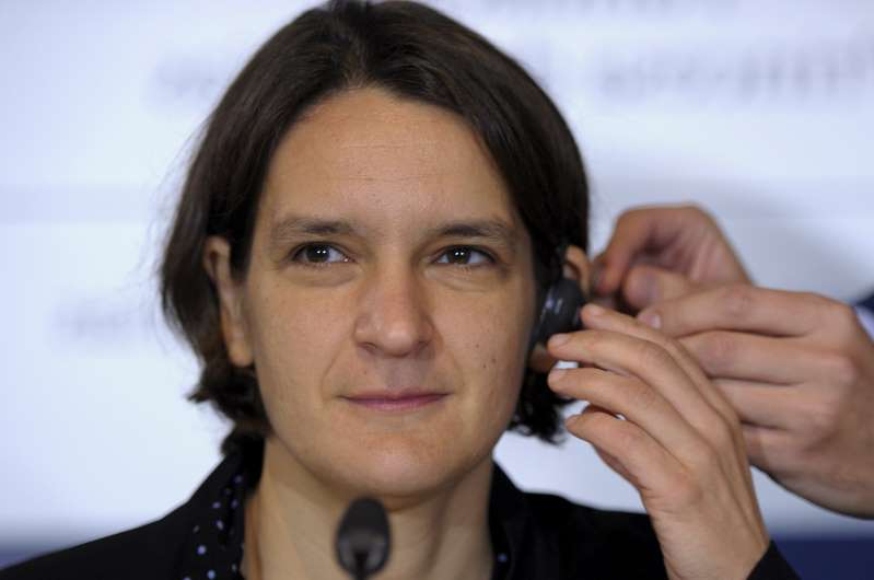 Esther Duflo talking on a cell phone: French economist Esther Duflo gets fitted with an earphone before a news conference in Oviedo,