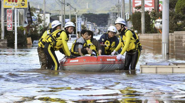 Slide 1 of 57: Local residents sit in a boat as they are rescued from a flooded residential area following Typhoon Hagibis on Oct. 13, in Iwaki, Fukushima prefecture, Japan.