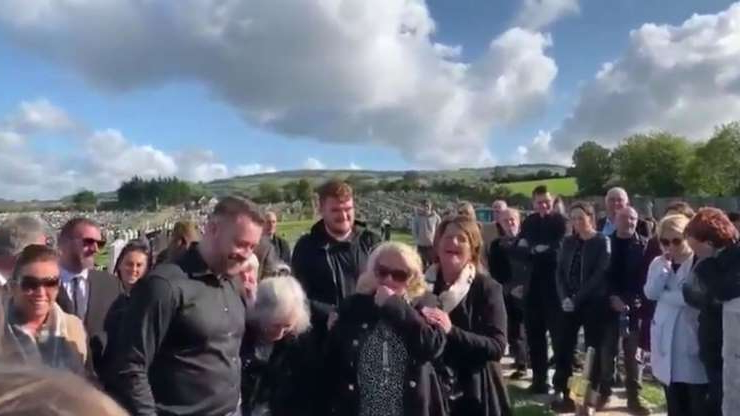 a group of people standing in front of a crowd posing for the camera: Mourners laugh as Shay Bradley's voice can be heard from beyond the grave