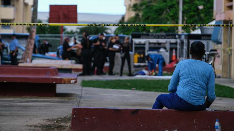 a person sitting on a bench in front of a building: Investigators on Tuesday at the site of a shooting at the Ernesto Ramos Antonini housing complex in the Río Piedras neighborhood of San Juan, P.R.