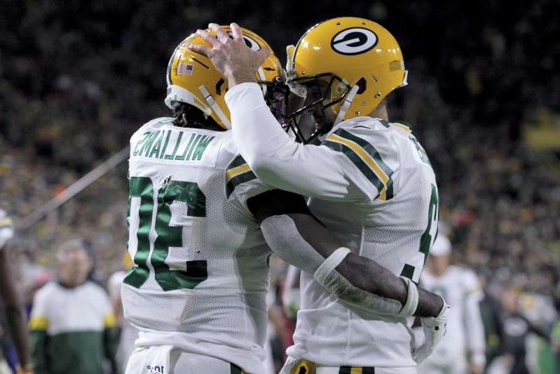 a person wearing a costume: Aaron Rodgers and Jamaal Williams celebrate after a touchdown against the Lions. (Getty Images)