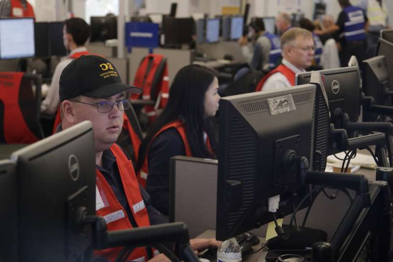 In this Oct. 10, 2019, file photo, Pacific Gas & Electric employees work in the PG&E Emergency Operations Center in San Francisco. Experts say it's hard to know what might have happened had the power stayed on, or if the utility's proactive shutoffs are to thank for California's mild fire season this year.