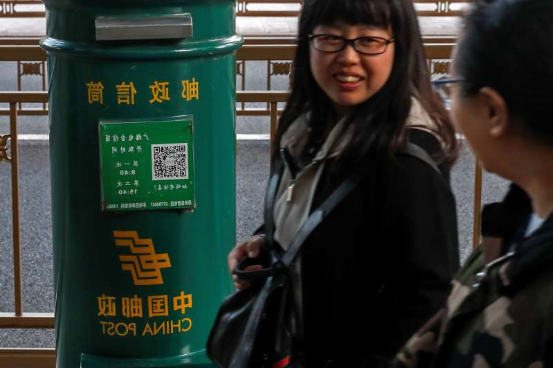 Women walk by a China Post mailbox in Beijing, Tuesday, Oct. 15, 2019. On Tuesday, China says fees it pays to the United States and other countries to deliver packages will nearly triple through 2025 under an agreement following complaints by Washington.  (AP Photo/Andy Wong)
