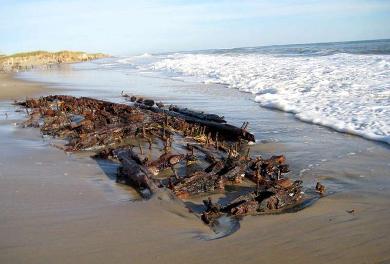 a group of people on a beach near a body of water: A recent storm on the Outer Banks unearthed an old shipwreck buried on the beach in Hatteras Island. The Wreck Tiki Bar in Hatteras, N.C. shared photos on Facebook.