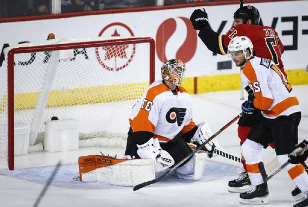 a group of people riding skis across snow covered ground: Philadelphia Flyers goalie Brian Elliott, right, reacts to a goal as Calgary Flames' Milan Lucic, centre, celebrates and Scott Laughton skates away during the second period of an NHL hockey game Tuesday, Oct. 15, 2019, in Calgary, Alberta. (Jeff McIntosh/The Canadian Press via AP)