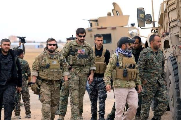 a group of people standing in front of a military uniform: Syrian Democratic Forces and U.S. troops patrol near the Turkish border in Hasakah, Syria, in 2018. The countries share a border of 822 kilometres.