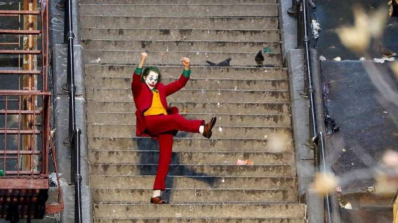 a person riding on the back of a red brick building: Joaquin Phoenix as the Joker, doing his dance of empowerment.