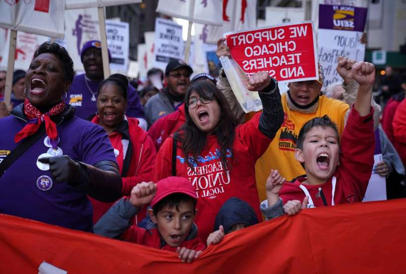 Emil Minty et al. posing for the camera: Chicago Teachers Union and SEIU members march through the Loop in Chicago on October 14, 2019.