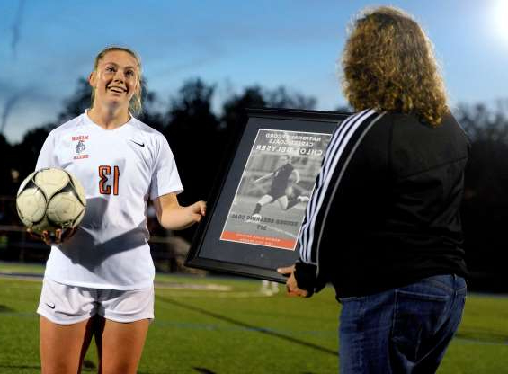 Slide 3 of 10: Marion girls soccer coach Lori DeLyser, left, presents a plaque and game ball to Chloe DeLyser after Chloe DeLyser scored her 317th career goal last night to set the national high school record.
