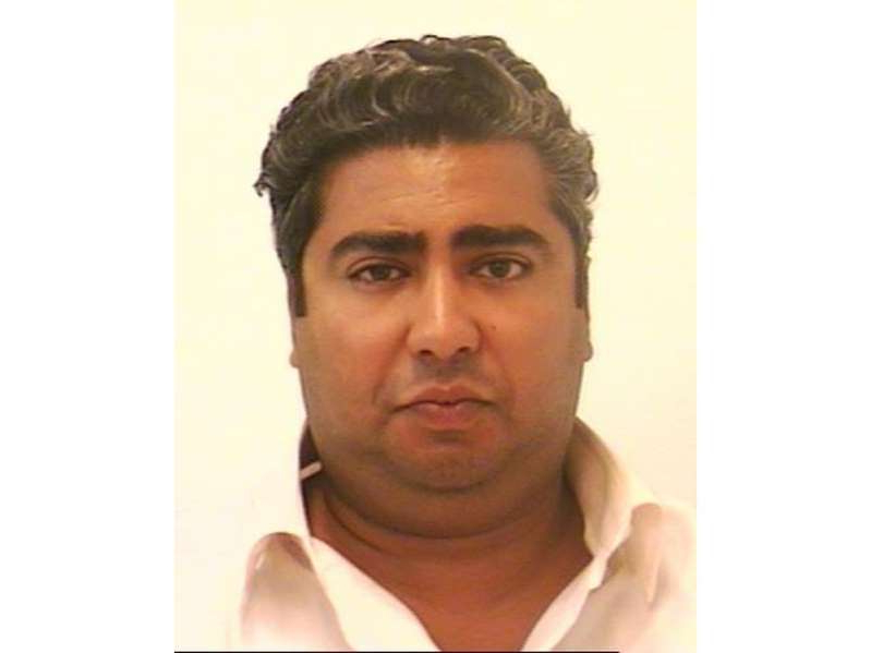 a man wearing a white shirt: Police booking photo of Fadi Saleh.