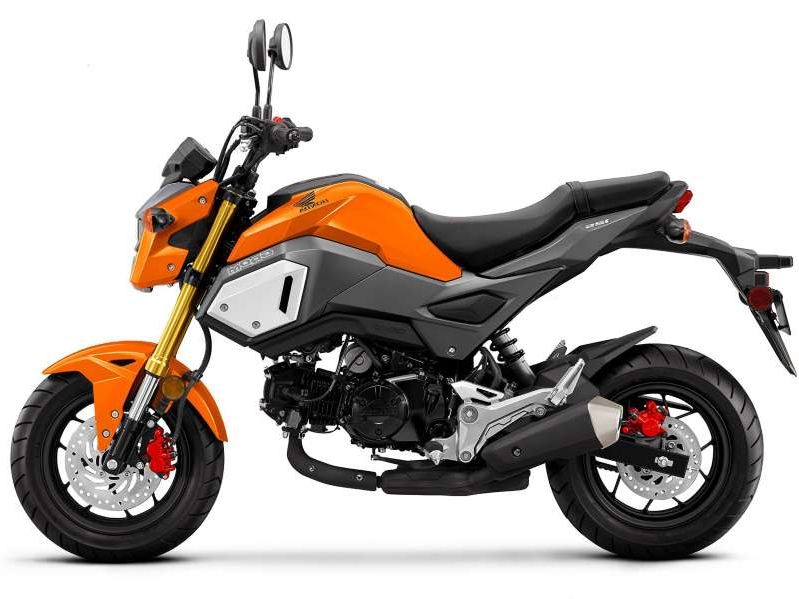 a motorcycle parked on the side: As Honda announced last May, the Grom will be returning to the 2020 miniMOTO category with new colors, like this Halloween Orange.