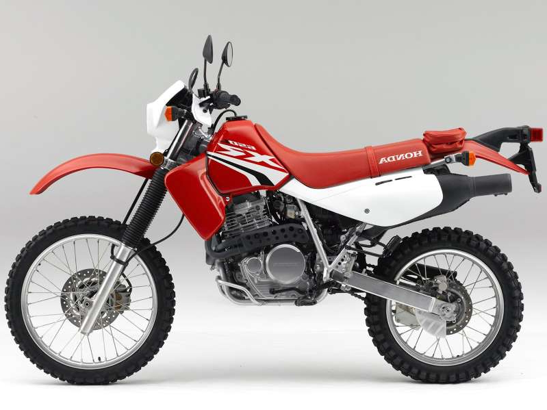 a red and black motorcycle is parked on the side of a dirt road: The Baja-flavored XR650L dual sport returns to Honda's 2020 US model lineup.