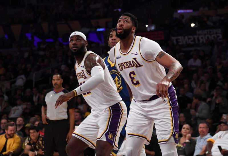 Anthony Davis, LeBron James are posing for a picture: Lakers forward Anthony Davis (3) and forward LeBron James (23) shown n the first half against the Warriors at Staples Center.