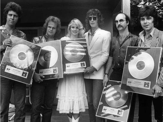 Dorothy Stratten et al. posing for a photo:  May 29, 1980 – Canadian rock band Prism is pictured with Playmate Dorothy Stratten.