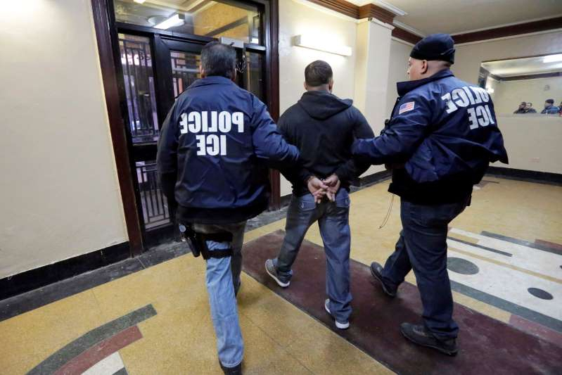 Immigration and Customs Enforcement officers escort an arrestee in an apartment building, in the Bronx borough of New York, during a series of early-morning raids.