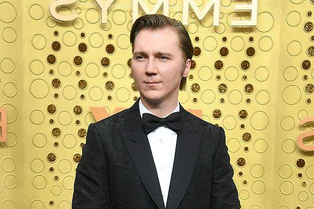 Paul Dano wearing a suit and tie standing in front of a curtain