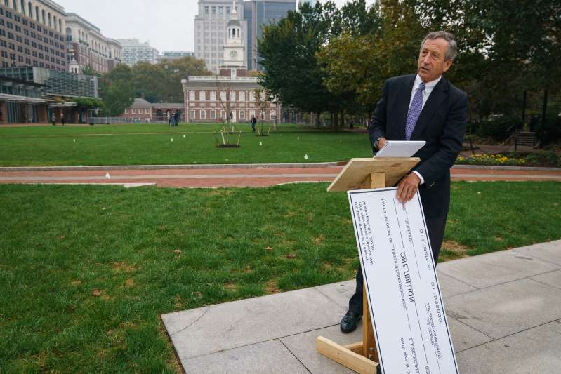 Republican Presidential Candidate Mark Sanford places a large check against a podium while preparing for a sparsely attended press conference at the People�s Plaza at Independence National Historical Park and Liberty Bell Center, during Sanford's campaign stop while running for president against Donald Trump, in Philadelphia, October 16, 2019. The check symbolizes Sanfords concern about the current deficit.