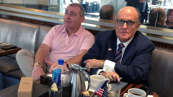 Rudy Giuliani et al. sitting at a table: President Trump's personal lawyer Rudy Giuliani with Ukrainian-American businessman Lev Parnas at the Trump International Hotel in Washington, D.C., Sept. 20, 2019.