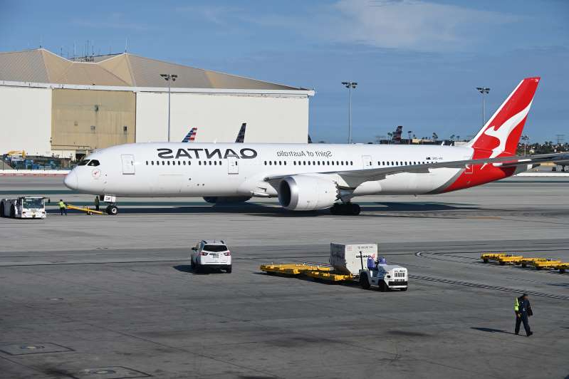 a airplane that is parked on the tarmac at an airport: A Boeing 787-9 Dreamliner from Qantas Air Lines