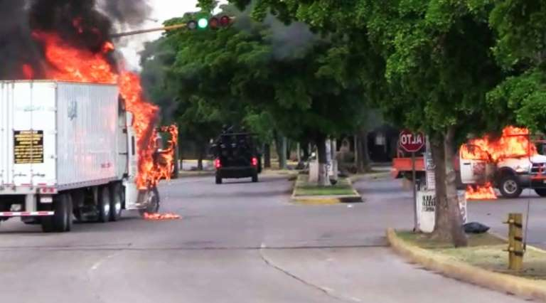 a fire truck driving down a street: Trucks burn in Culiacan, capital of jailed Mexican druglord Joaquin