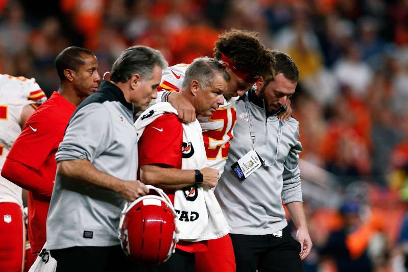 a group of baseball players playing a football game: Chiefs quarterback Patrick Mahomes is helped off the field after suffering a knee injury in the second quarter against Denver on Thursday.