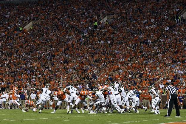 a group of people running in front of a crowd: CLEMSON, SOUTH CAROLINA SEPTEMBER 21: Place kicker B.T. Potter #29 of the Clemson Tigers kicks a field goal during the first quarter of the Tigers' football game against the Charlotte 49ers at Memorial Stadium on September 21, 2019 in Clemson, South Carolina.
