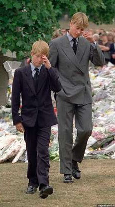 a group of people standing next to a person in a suit and tie: Prince William, left, and Prince Harry gesture after they arrived at Kensington Palace to view some of the flowers and mementos left in memory of their mother Princess Diana in London in 1997