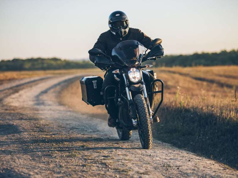 a man riding a motorcycle down a dirt road: The 2020 Zero DSR Black Forest is an industry first, electric-powered adventure bike that is making its way into a market segment dominated by gas-powered motorcycles.