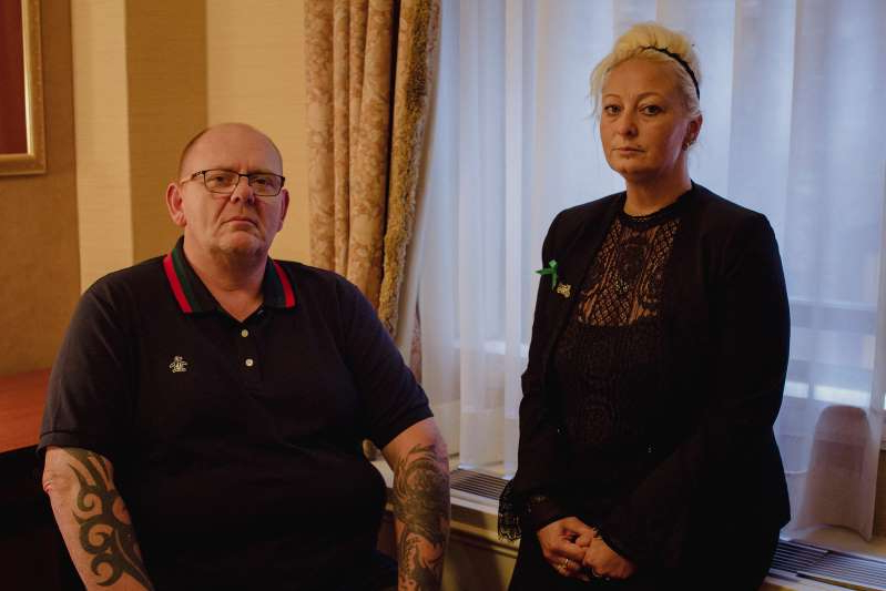 a man standing in a room: Charlotte Charles and Tim Dunn, the parents of Harry Dunn, a 19-year-old who was killed when a car crashed into his  motorbike on August 27. The suspect in the case, 42-year-old Anne Sacoolas, was granted diplomatic immunity after the crash, but Prime Minister Boris Johnson has asked the U.S. to consider waiving it.
