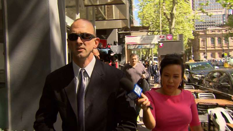 a man wearing a suit and tie talking on a cell phone: Andrew John Tanner outside court in Melbourne.