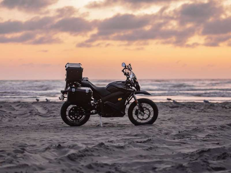 a motorcycle parked on top of a sandy beach next to the ocean: If you are looking to go a little ways off the beaten path, then the 2020 Zero DSR Black Forest might be the bike for you. Think of it as a legitimate entry-level adventure motorcycle that just happens to be electric.