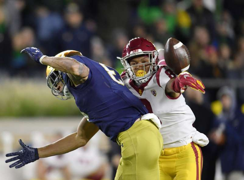 a person wearing a costume: USC Trojans cornerback Chris Steele (8) breaks up a pass in the first half intended for Notre Dame Fighting Irish wide receiver Chase Claypool (83) at Notre Dame Stadium.