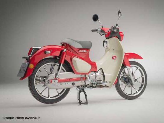 a red motorcycle parked next to a bicycle: The Super Cub gets just a new red color for 2020 and a higher price tag, but it keeps all the friendly features, like a low seat height, convenient cargo hold, and semi-auto transmission.