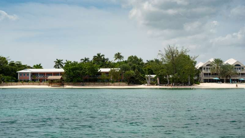 a small boat in a large body of water: Two properties owned by Mr. Dart on Grand Cayman. His portfolio includes the Ritz-Carlton, the Yacht Club and a Kimpton resort.