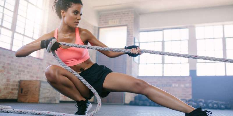"a woman standing in front of a window: When you hear ""high intensity interval training,"" you might imagine CrossFitters climbing ropes, but it's a great workout for everyone especially if you want to lose weight."