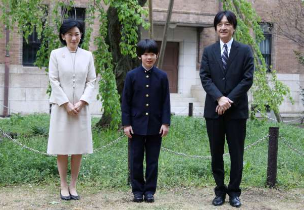 Prince Akishino, Prince Hisahito of Akishino standing next to a person wearing a suit and tie: FILE PHOTO: Prince Hisahito, accompanied by his parents Prince Akishino and Princess Kiko, poses for photos at Ochanomizu University junior high school before attending the entrance ceremony in Tokyo