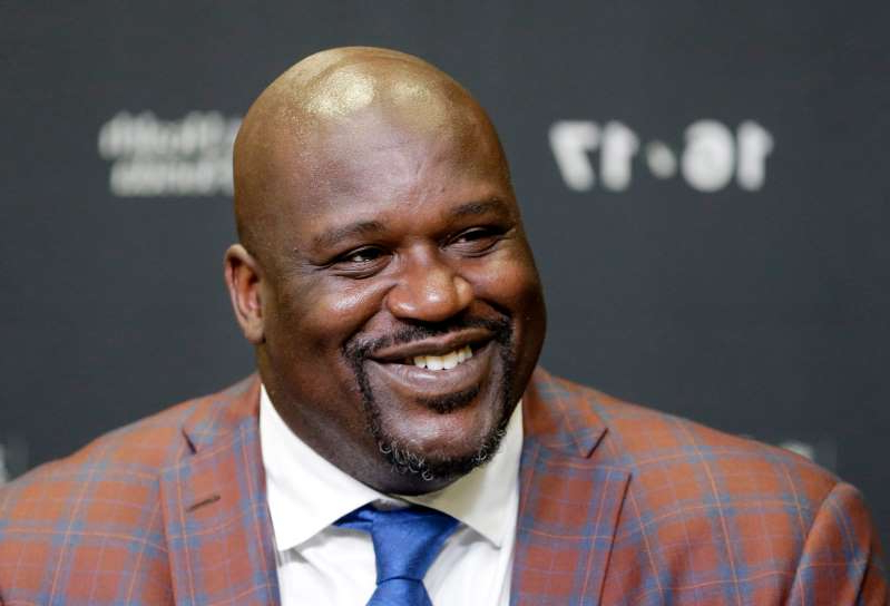 Shaquille O'Neal wearing a suit and tie: Hall of Fame basketball player Shaquille O'Neal smiles as he talks to reporters.