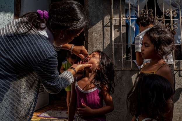 Slide 18 of 30: MANILA, PHILIPPINES - OCTOBER 14: A community health worker administers an oral polio vaccine to a child, during a mass vaccination campaign to combat the resurgence of the polio virus, in a slum area on October 14, 2019 in Manila, Philippines. The Philippines is aiming to vaccinate over 9 million children after the country's health department announced an outbreak of polio, 19 years after the World Health Organization declared the country free of the infectious disease. Health Secretary Francisco Duque has blamed poor immunization coverage and lack of proper sanitation and hygiene as the cause of the resurgence of the disease. The Philippines has been struggling to regain the publics trust in vaccines since 2017, when it was discovered that a dengue vaccine manufactured by French firm Sanofi could cause health risks to people who had not previously had the disease. Recently, the country declared a dengue epidemic after hundreds have died of the mosquito-borne disease. (Photo by Ezra Acayan/Getty Images)